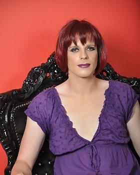 Sexy Cross-dresser wearing a purple dress & posing on the throne.